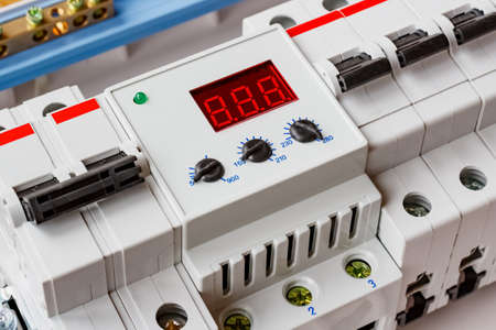 Voltage limiter with automatic circuit breakers closeup in the white plastic mounting box closeup Фото со стока