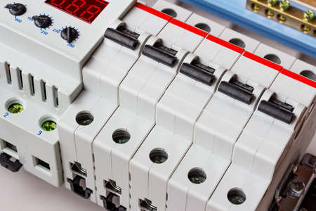 Automatic circuit breakers and voltage limiter on DIN rail in white plastic mounting box