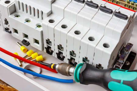 Automatic circuit breakers installed on DIN rail in white plastic mounting box on a background of wires and screwdriver Фото со стока