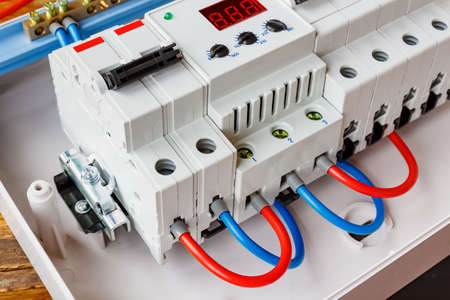Red and blue wires connected to the ports of voltage limiter and double input automatic circuit breaker closeup
