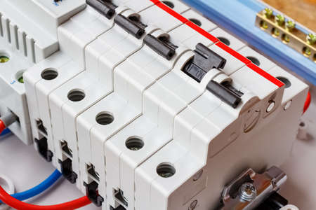 Installed automatic circuit breakers on DIN rail in white plastic mounting box closeup Фото со стока