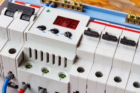 Voltage limiter and automatic circuit breakers closeup in the white plastic mounting box