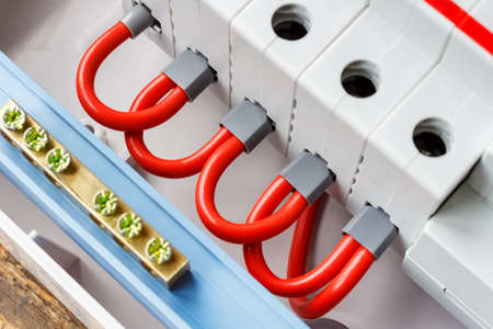 Ports of automatic circuit breakers connected by red wires closeup Banco de Imagens