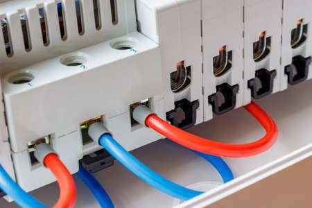 Anschlüsse der installierten Sicherungsautomaten, die durch rote und blaue Drähte verbunden sind, Nahaufnahme Standard-Bild