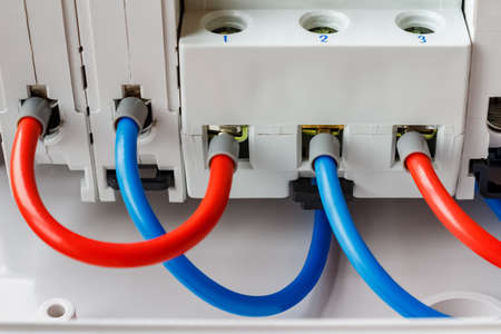 Ports of installed automatic circuit breakers connected by red and blue wires closeup