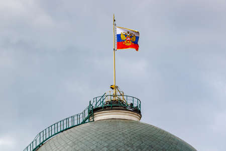 Flag of Russian Federation with gilded coat of arms waving on the dome of Senate Palace of Moscow Kremlin Stock fotó