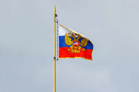 Waving flag of Russian Federation with gilded coat of arms against cloudy sky