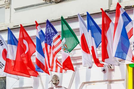 Flags of different countries posted in a row on the building wall in sunny day Stock fotó