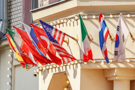 Flags of different countries in holders on building wall