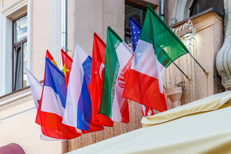 Waving flags of different countries in a row on the wall in sunlight Stock fotó