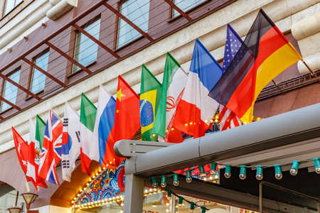 Many flags of different countries on the wall in a row close-up