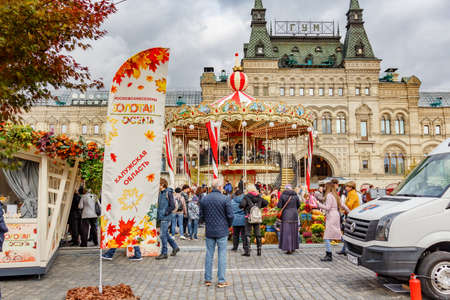 Moscow, Russia - October 05, 2019: View of decoreted two-storey carousel against facade of GUM State Department Store. Attraction on the traditional festival Golden Autumn on Red Square in Moscow