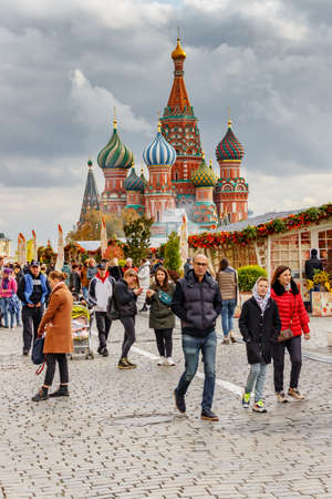 Moscow, Russia - October 05, 2019: People walking on Red Square against decorations of the traditional festival Golden Autumn. Moscow downtown at cloudy autumn day