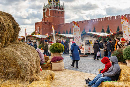 Moscow, Russia - October 08, 2019: Territory of a traditional festival Golden Autumn on Red Square in sunlight. Visitors walking against trade pavilions