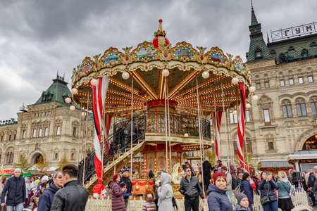 Moscow, Russia - October 05, 2019: Two-storey carousel on the traditional festival Golden Autumn on Red Square in Moscow against GUM State Department Store