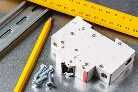 White automatic circuit breaker lying on shiny metal mounting plate of electrical panel with yellow pencil and ruler. Electrical panel assembling