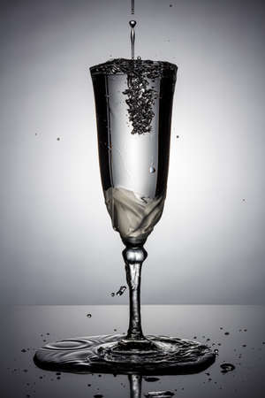 Frozen water jet with splashes and flying water drops in full champagne glass on a thin high leg in white backlight with reflection on a dark glossy surface. Stop motion photography