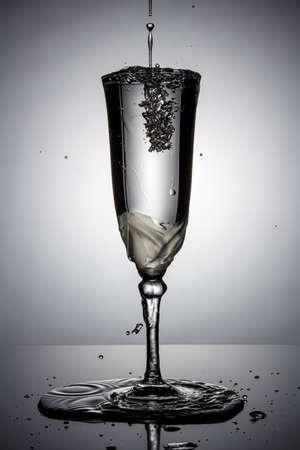 Gefrorener Wasserstrahl mit Spritzern und fliegenden Wassertropfen in vollem Champagnerglas auf einem dünnen hohen Bein in weißer Hintergrundbeleuchtung mit Reflexion auf einer dunklen glänzenden Oberfläche. Stop-Motion-Fotografie