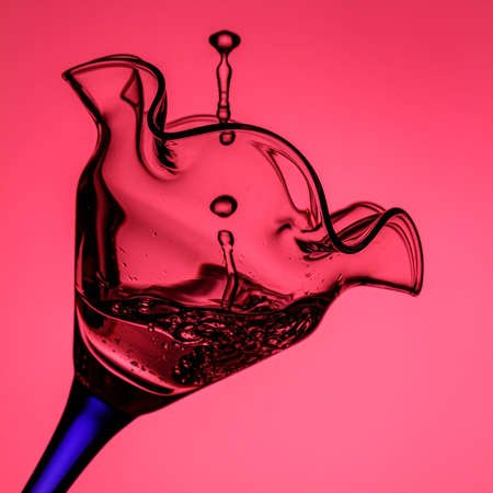 Tilted cocktail glass on blue leg with frozen water jet and splashes close-up in pink backlight. Stop motion photography