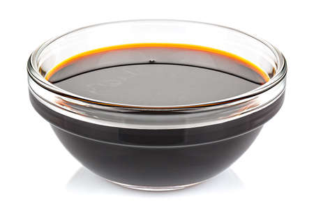 Soy sauce in a small transparent glass round bowl isolated on white background Banque d'images