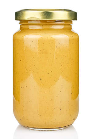 Mustard in a transparent glass jar with a closed gilded metal lid isolated on white background