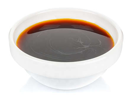 Soy sauce in a small white ceramic round bowl isolated on white background