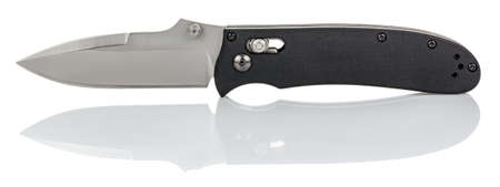 Side view of open folding pocket knife with satin blade and black composite plastic cover plates on steel handle isolated on white background with reflection on glossy surface. Pocket knife close-up