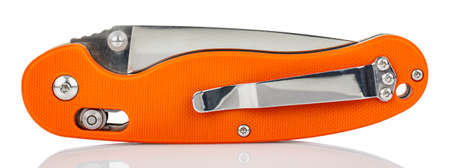 Side view of closed folding pocket knife with textured bright orange composite plastic cover plates on steel handle isolated on white background with reflection on glossy surface. Pocket knife image