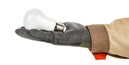 Round LED lamp lies in palm of electrician hand in black protective glove and brown uniform isolated on white background