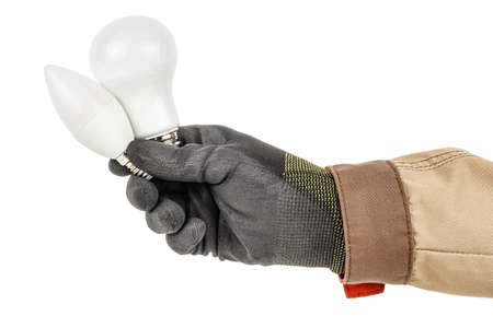 Two modern LED lamps in electrician hand in black protective glove and brown uniform isolated on white background Standard-Bild - 147596512