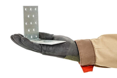 Galvanized metal mounting bracket with holes lies in palm of worker hand in black protective glove and brown uniform isolated on white background