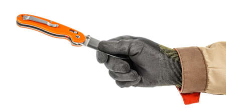 Worker hand in black protective glove and brown uniform holding by fingers blade of open pocket knife with bright orange handle isolated on white background