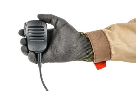 Man hand in black protective glove and brown uniform holding walkie talkie handheld microphone isolated on white background