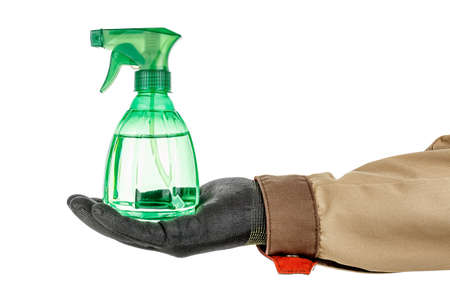 Green transparent plastic spray bottle with liquid standing on palm of man hand in black protective glove and brown uniform isolated on white background Stok Fotoğraf
