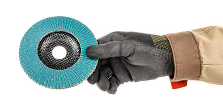 Man hand in black protective glove and brown uniform holding by fingers blue abrasive flap disc for grinding isolated on white background