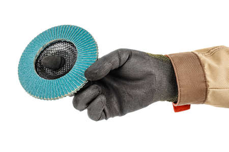Worker hand in black protective glove and brown uniform holding blue abrasive flap disc for grinding isolated on white background Stockfoto