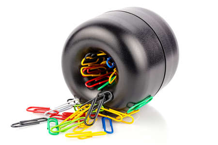 Lying cylindrical black plastic magnetic holder with colored paper clips isolated on white background Banque d'images
