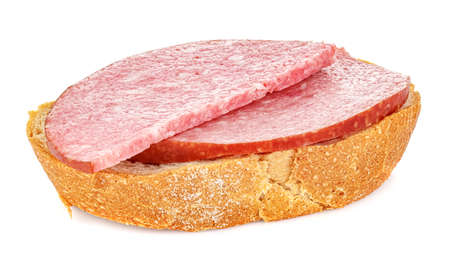 Piece of fresh rye bread with two slices of smoked sausage isolated on white background