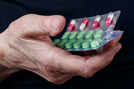 Blister packs with colored pills in elderly woman palm on black background