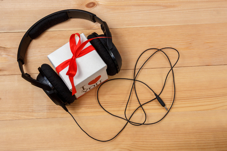 studio background: Gift box with headphones on wooden table. Top view.
