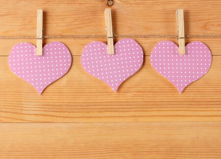 symbolics: Handmade hearts hanging on rope against wood-grain wall