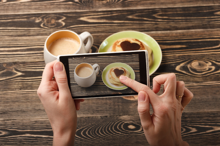 maslenitsa: Hands taking photo pancakes with a smartphone