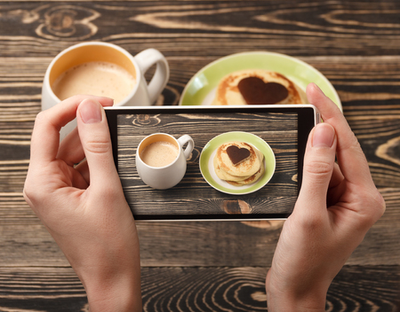 Hands taking photo pancakes with a smartphone