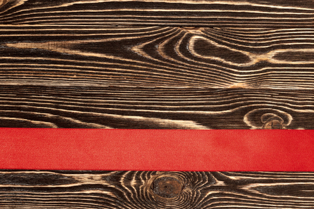 horizontally: Red ribbon horizontally placed on wooden background