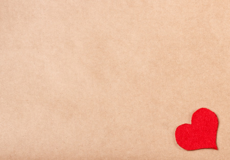 background pattern: red handmade heart on brown paper craft