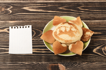 shrove: heart-shaped pancakes with blank card on wooden table, Shrove Tuesday, Valentines Day Stock Photo