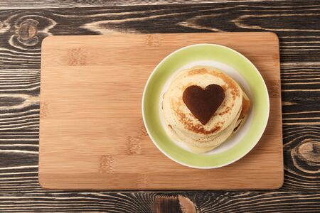 shrove tuesday: stack of pancakes with on brown wooden board, heart-shaped, Shrove Tuesday, Valentines Day Stock Photo