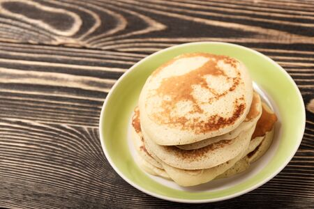 shrove: stack of pancakes on brown wooden board Stock Photo