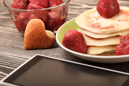 pasteurized: smartphone, Pancakes, strawberries on brow wooden table Stock Photo