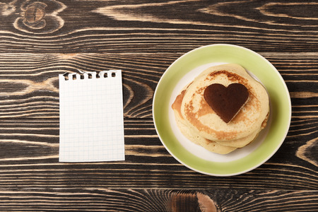 shrove tuesday: heart-shaped pancakes with blank card on wooden table, Shrove Tuesday, Valentines Day Stock Photo